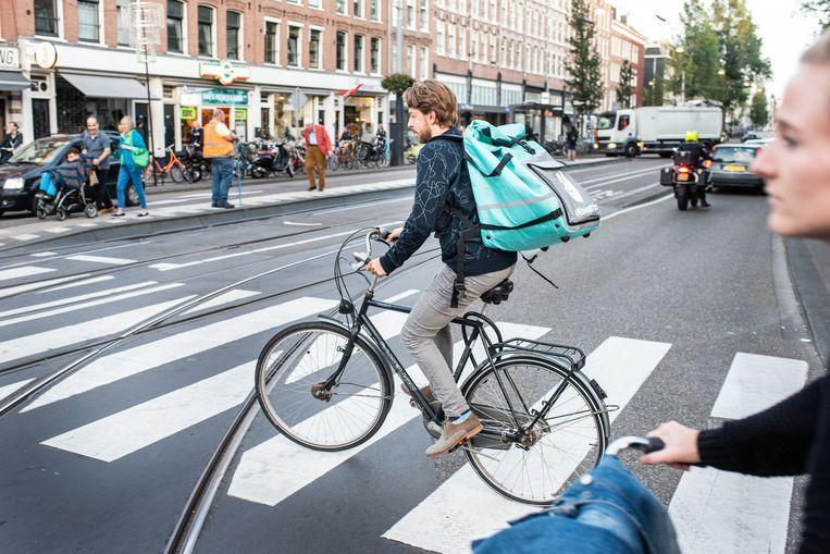 Volkskrant-verslaggever Joost de Vries werkte als fietskoerier voor Deliveroo. De FNV vraagt zich af of jongeren die dit werk doen de voorgestelde premie kunnen betalen. Beeld Simon Lenskens