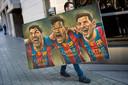MSN: Een man draagt in 2017 een schilderij met de hoofden van Luis Suárez, Neymar en Lionel Messi.
