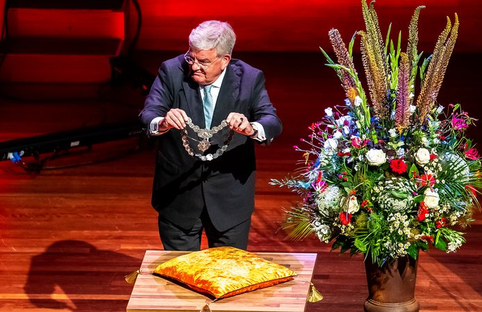 Jan van Zanen doet symbolisch zijn ambtsketen af.