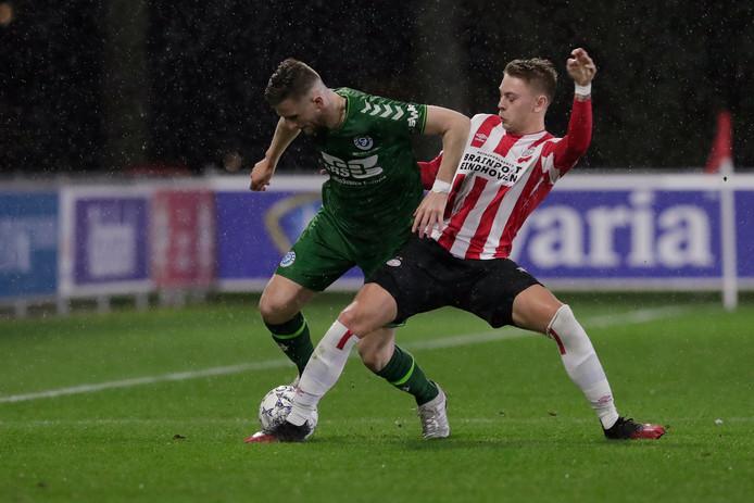 Branco van den Boomen van De Graafschap in duel met Robin Schoonbrood van Jong PSV.