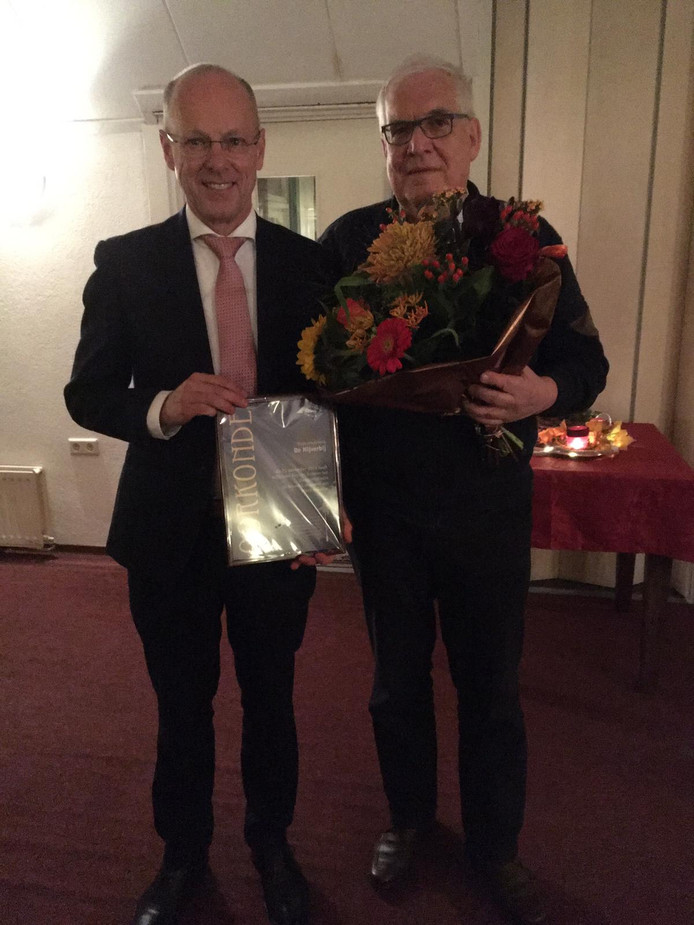 Wethouder Bas van Wakeren (links) reikt het Hengelose compliment De Nijverbij uit aan Harry Holstijn.