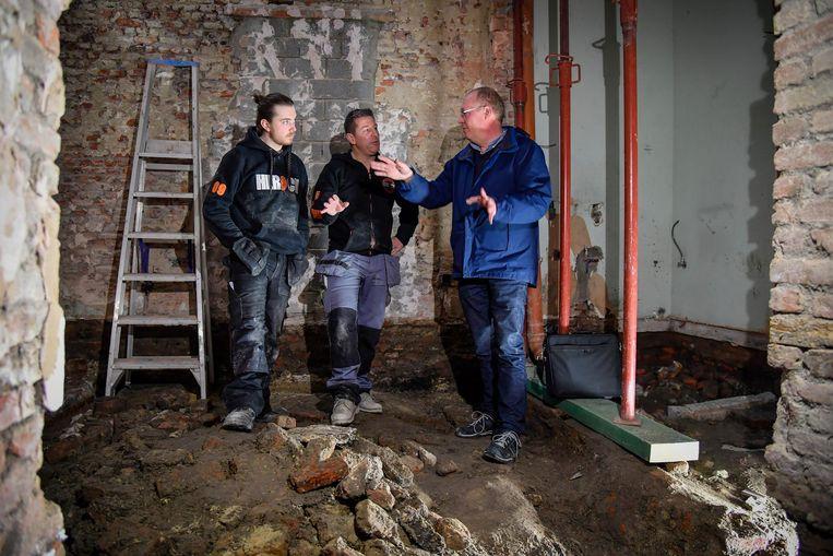 Nico Peelman en zoon Marijn Peelman bespreken de vondst met een van de archeologen.