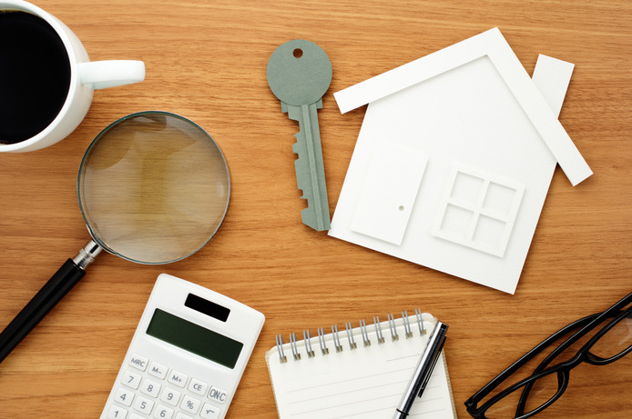 House and key shaped paper cutout, calculator and magnifier on wooden table. stockadr huis woning wonen