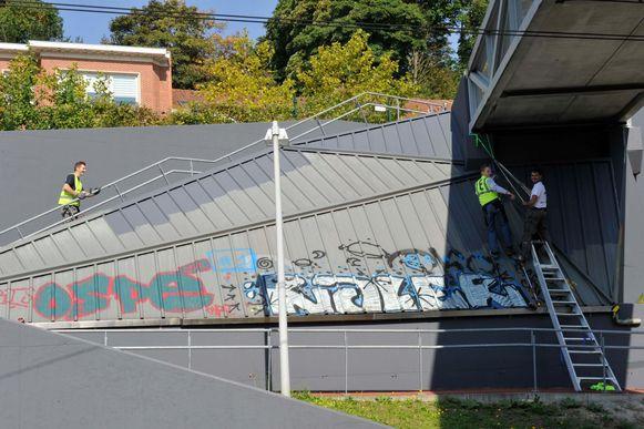 De illegale graffiti wordt overschilderd met een heus graffiti-kunstwerk.
