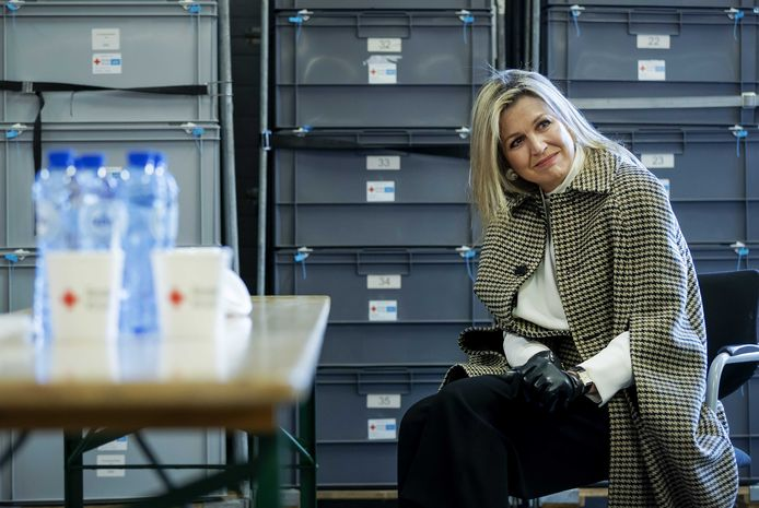 Koningin Máxima luistert aandachtig naar de verhalen van vrijwilligers van het Rode Kruis.