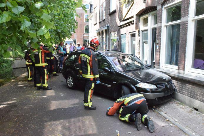 Hulpdiensten bekijken de situatie, nadat een auto tegen een gevel is geklapt.