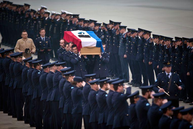 Militairen dragen een kist met de Nederlandse vlag bij aankomst van de twee bij het Apache-ongeluk omgekomen militairen.    Beeld null