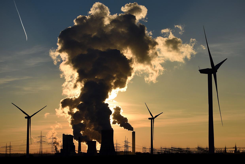 Windturbines en een oude steenkoolcentrale staan zij aan zij in het Duitse Bergheim. De Europese Green Deal moet een eind aan die rookpluimen maken.