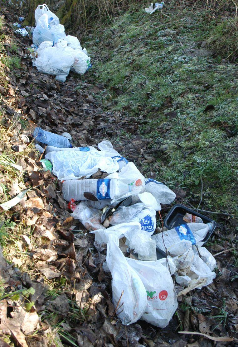 De bermen liggen bezaaid met petflessen, plastic zakjes en ander afval.