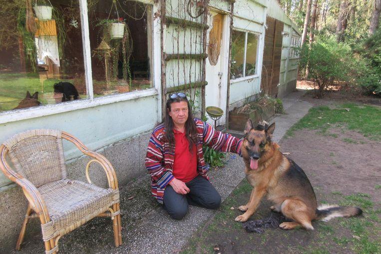Bruno De Clercq met zijn hond Shiva voor de chalet.