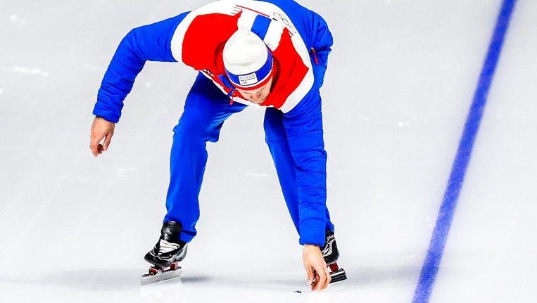 De bondscoach van de Noorse schaatsploeg Sondre Skarli raapt de afgebroken veer van de schaats van Jan Blokhuijsen van het ijs. Beeld anp
