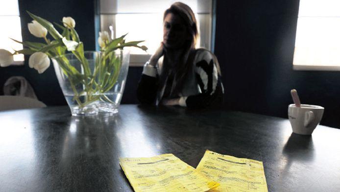 Majorie van Espelo thuis aan tafel achter haar bekeuringen. Ze snapt niks van de manier waarop ze is behandeld.