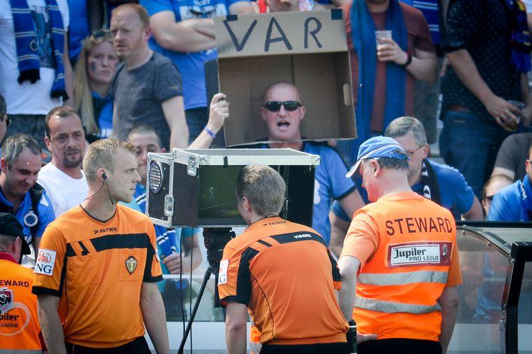 Ludieke Brugse fan in de tribunes terwijl Lawrence Visser op aanbeveling van zijn videoref naar de beelden kijkt.