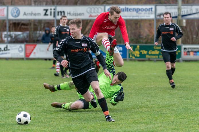Lars Hogenkamp en Leon Brandts van SV Angeren voorkomen dat Jonge Kracht-speler Gijs Thuis gevaarlijk kan worden.