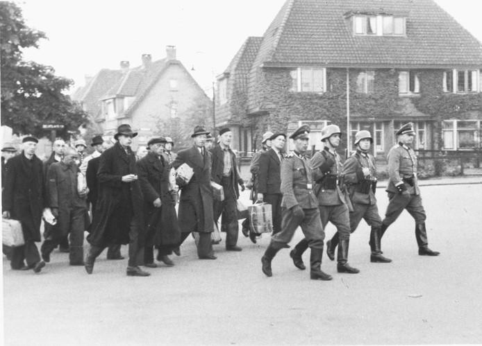 De mannen uit Putten lopen in een grote stoet, onderweg naar een concentratiekamp.