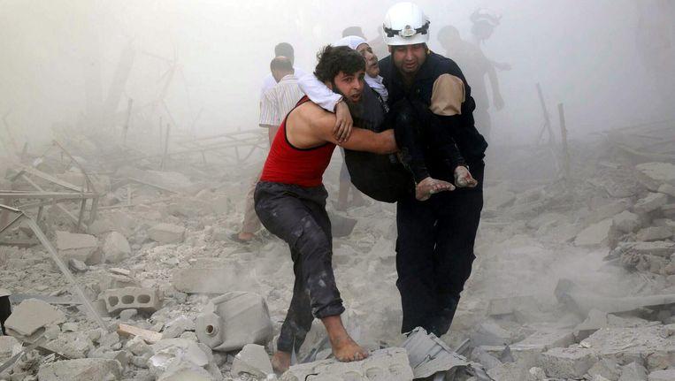 Vrijwilligers van de Witte Helmen in actie na een bomaanval. De organisatie zegt te werken voor alle groepen slachtoffers Beeld EPA