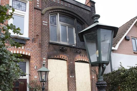 De ramen van de benedenverdieping zijn dichtgetimmerd. De bovenramen en de gevel zijn zwartgeblakerd.