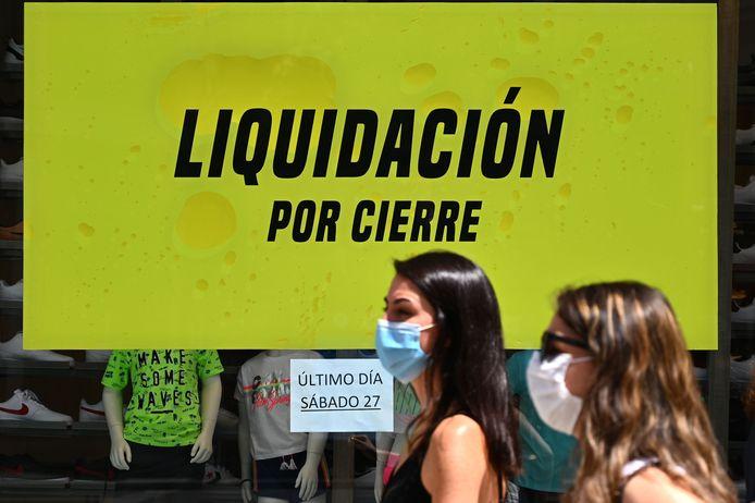 Vrouwen lopen langs de etalage van een winkel in Madrid die opheffingsuitverkoop houdt vanwege de coronacrisis. Vrouwen werken vaker in sectoren als detailhandel en toerisme, die zwaar worden getroffen.