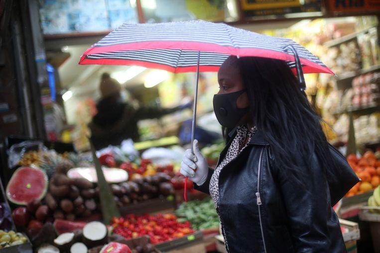 Een vrouw die zich beschermt met een mondkapje loopt door de multiculturele Londense wijk Brixton. Onder de slachtoffers van het coronavirus zijn verhoudingsgewijs veel mensen met een migratieachtergrond. Beeld Hannah McKay / Reuters