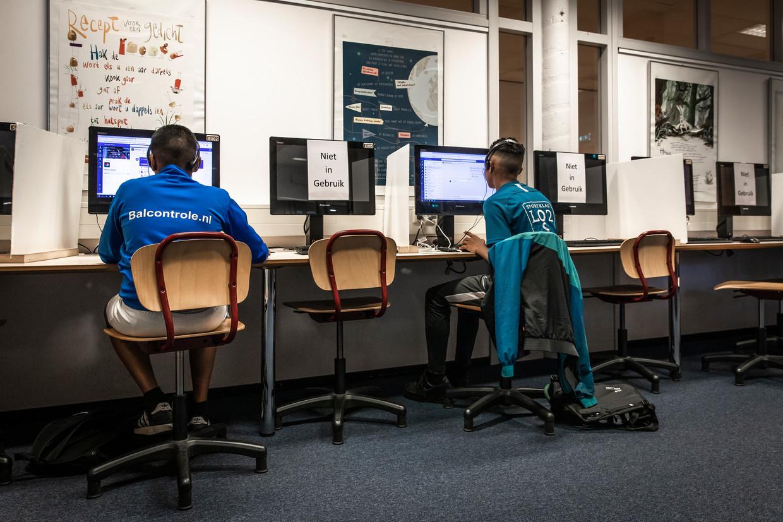 Op meerdere computers kan niet worden gewerkt en tussen de plekken staan schotten van karton.  Beeld Dingena Mol