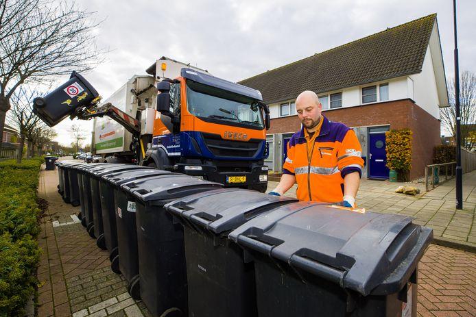 Patrick van der Weegen van Afvalstoffendienst Den Bosch zet de grijze containers van Rijstveld in Empel zo neer dat deze makkelijk per twee te legen zijn.