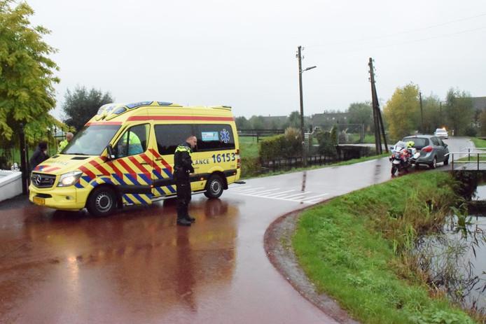 Een gewonde fietsster wordt in de ambulance behandeld na een botsing met een auto in Bergambacht.