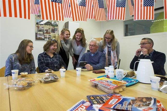 Lotte, Anne, Ilse, Nienke en Larissa (van linksaf) bekijken het Amerikaanse paspoort van Sam Terpstra. Zij volgden woensdagochtend samen met hun leraar Erik Braaksma (rechts) en 25 medeleerlingen de verkiezingsuitslagen in Amerika.