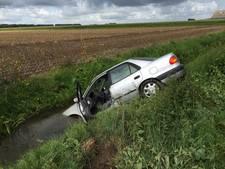 Modder op de weg: auto glijdt in de sloot in Drimmelen