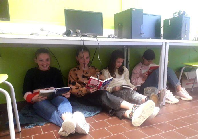 Enkele meisjes nestelen zich onder de tafels voor het lezen van een boek