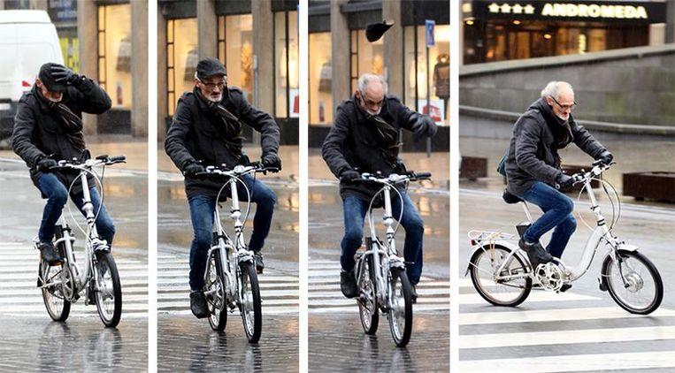 De wind blaast het petje van het hoofd van deze fietser, maar de man rijdt gewoon door.