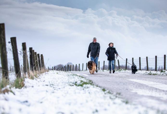 In delen van Nederland is vannacht de eerste sneeuw van deze winter gevallen. Twee mensen liepen vanochtend door de sneeuw met hun honden.