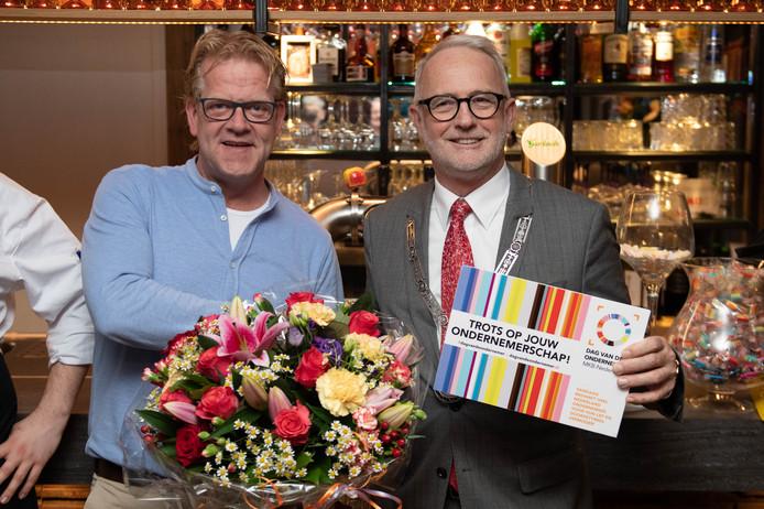 Burgemeester Gerard van den Hengel (rechts) overhandigt een blijk van waardering aan eigenaar Lereau Hulsink van restaurant Hertme's Ambacht.