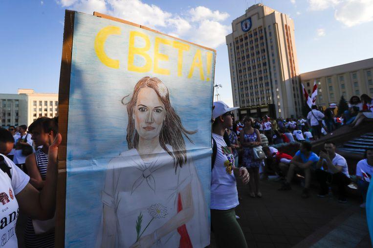 Mensen dragen een portret van oppositiekandidaat Svetlana Tichanovskaja. Beeld AP