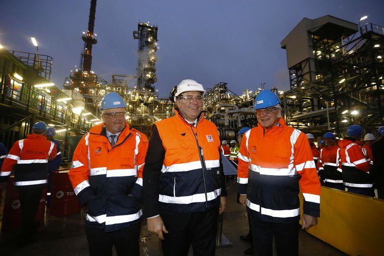 Marc Van Peel, CEO van Total Patrick Pouyane en Kris Peeters, met achter hen de vernieuwde raffinaderij.