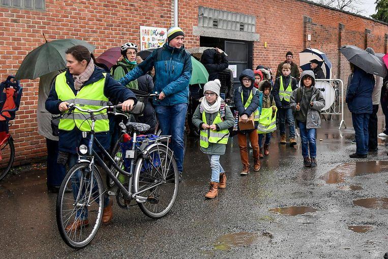Ouders en leerlingen aan de schoolpoort in de Werkplaatsstraat. De knip werd er weggehaald. Na protest komt er nu een neerklapbare paal.