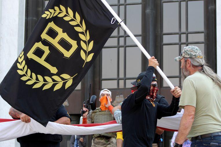 Een activist zwaait de vlag van de Proud Boys, een rechtse groep, voor het parlementsgebouw van de Amerikaanse staat Oregon. Trump zei over hen: 'Stand back and stand by' – 'Stop nu, maar blijf paraat'.  Beeld AP