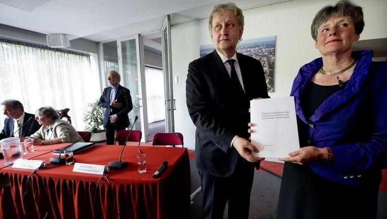 Burgemeester Eberhard van der Laan en voorzitter Louise Gunning-Schepers van de commissie-Gunning poseren het rapport van het onderzoek naar de zedenzaak in Amsterdam. Foto ANP Beeld anp