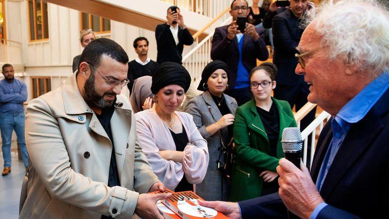Henk Spaan overhandigt het eerste exemplaar aan Nouri's vader. Beeld anp