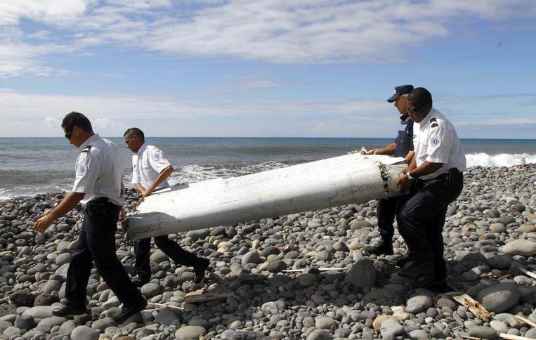 Politieagenten dragen een wrakstuk op het eiland Réunion. Beeld null