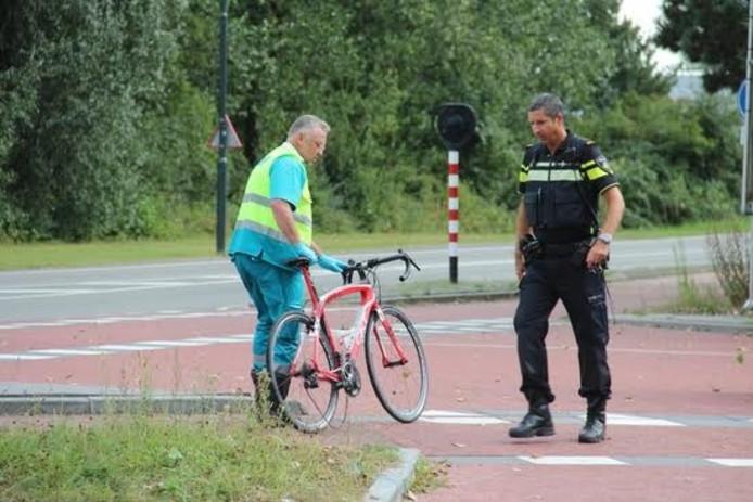 Een hulpverlener met de wielrenfiets van het slachtoffer.