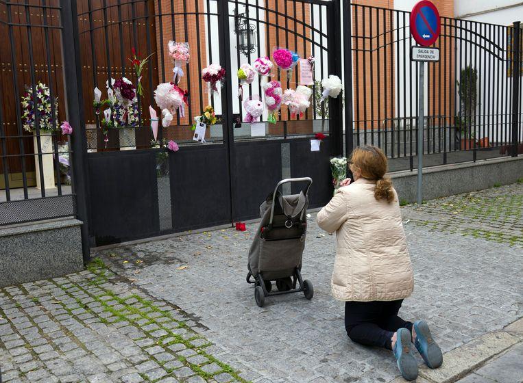 Een vrouw knielt voor de El Cerro kerk in het Spaanse Sevilla. Een Goede Week-processie werd hier geannuleerd vanwege het coronavirus. Beeld AP