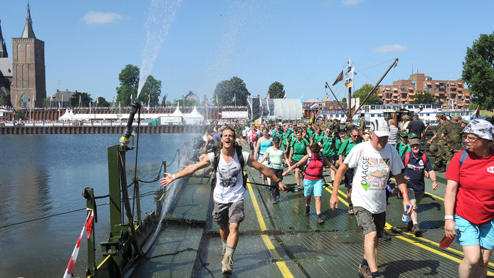 Vierdaagselopers nemen bij Cuijk via een ponton de oversteek over de Maas.