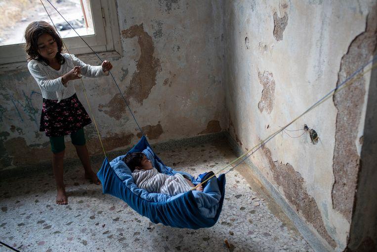 Grote zus wiegt een twee maanden oude Afghaanse baby in een verlaten pand op het eiland Lesbos.