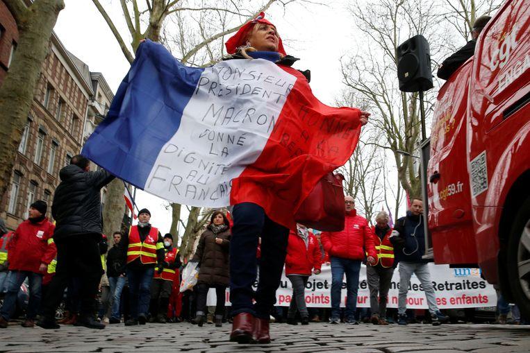 Van Parijs tot Marseille gaan werknemers de straat op om de pensioenplannen van president Macron van tafel te krijgen. In Lille toont een demonstrant de Franse vlag met een oproep aan Macron .  Beeld REUTERS