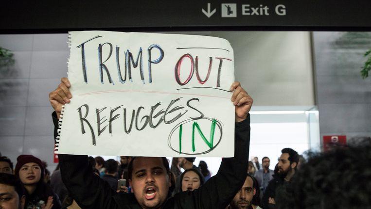 Op verschillende Amerikaanse vliegvelden, zoals hier in San Francisco, protesteren betogers tegen de detentie van reizigers uit de zeven moslimlanden die Trump de komende drie maanden in de ban heeft gedaan. Beeld EPA