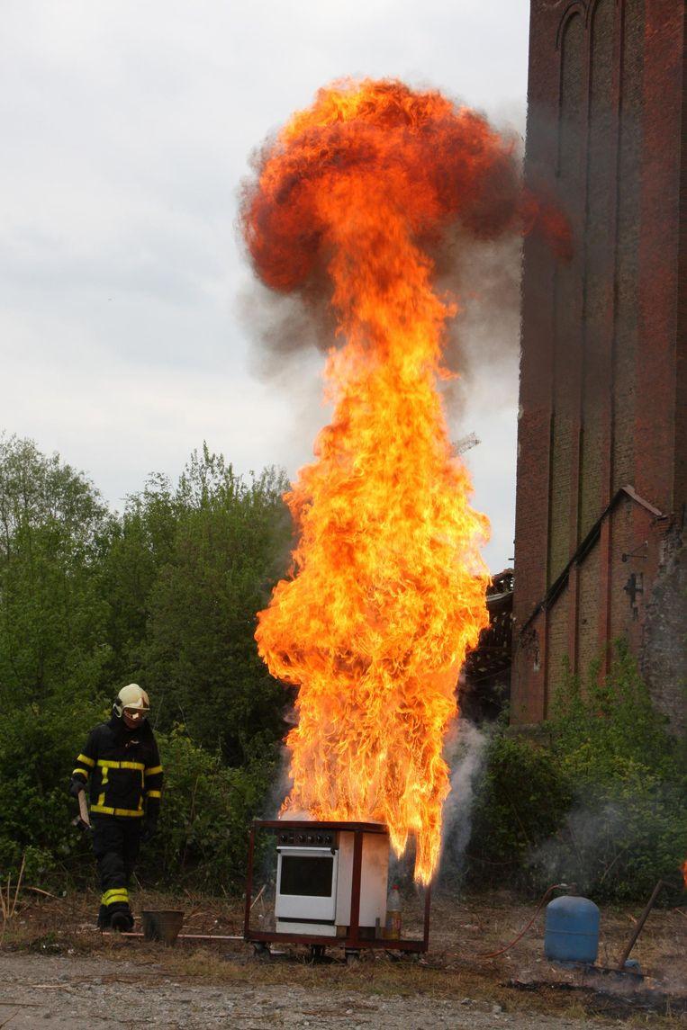 De brandweer toont wat er gebeurt als je een brandende friteuse met water blust.