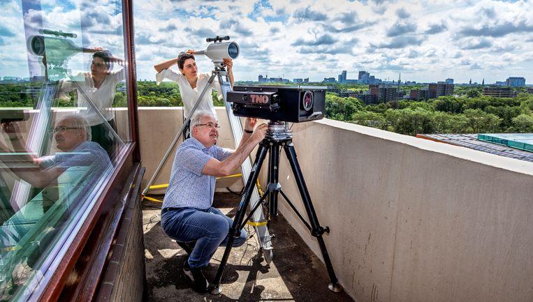 Pascal Paulissen (onder) en Federica Valente werken aan een laseropstelling bij TNO. Beeld Raymond Rutting/ de Volkskrant