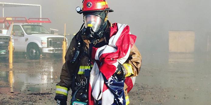 Een brandweerman in Phoenix, in de staat Arizona, met een natgespoten Amerikaanse vlag.
