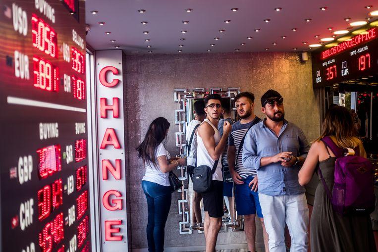 Mensen bekijken de wisseltarieven bij een wisselkantoor in Istanbul.  Beeld Joris Van Gennip