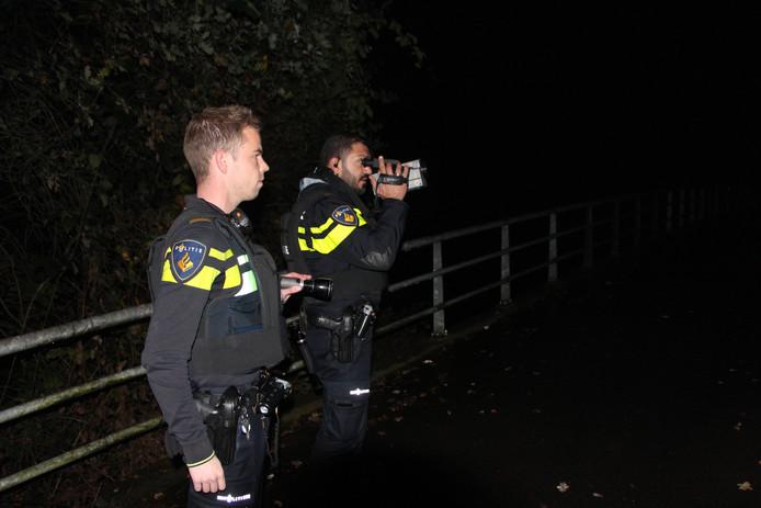 Politieagenten speuren met een warmtebeeldcamera naar de gevluchte overvaller